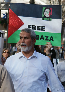 Senior man with white beard in protest march, Palestinian flag sign behind him.