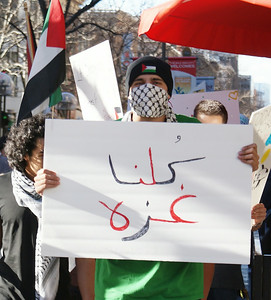 Young man wearing keffiyeh over face, carries sign with Arabic writing on it, other protest marchers behind him.