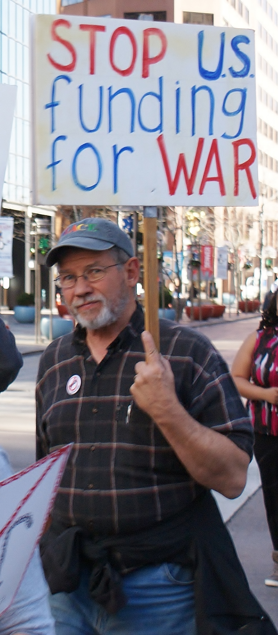 Man marching with sign about US war funding.