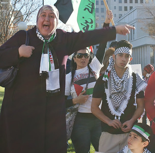 Woman wearing hijab and Palestinian flag scarf gestures while speaking at rally, young man wearing keffiyeh next to her.