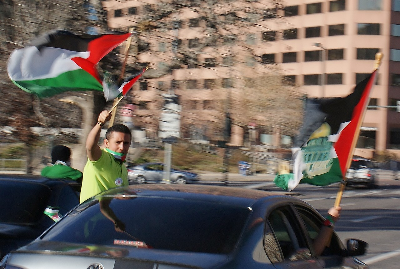 Young man leans out of window of moving car, waving Palestinain flag.