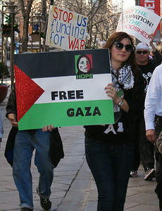 Young woman marching with sign depicting Palestinian flag, other protesters in background.