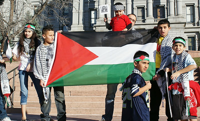 Father lifts up young child and young boys display Palestinian flag.