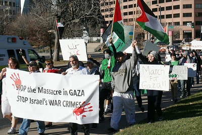 Protesters carry large banner about Israeli attack on Gaza, large group of demoinstrators march behind them.