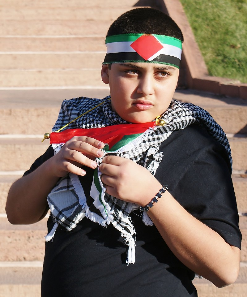Young boy wearing keffiyeh and Palestinian flag headband.