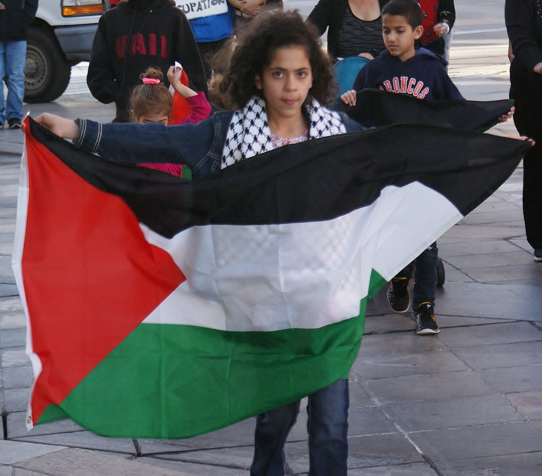 Young girl walking, carrying large Palestinian flag in front of her.
