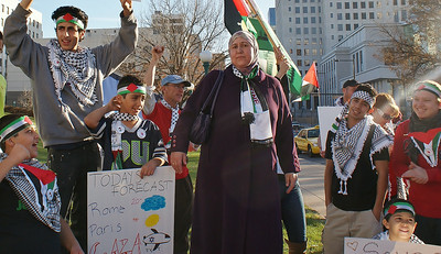 Woman wearing hijab and Palestinian flag scarf,young boys wearing keffiyehs standing around her, one raising hands in air.