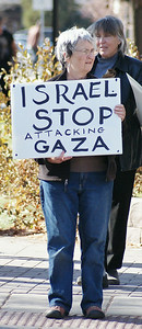 senior woman holding sign protesting Israeli attack on Gaza.