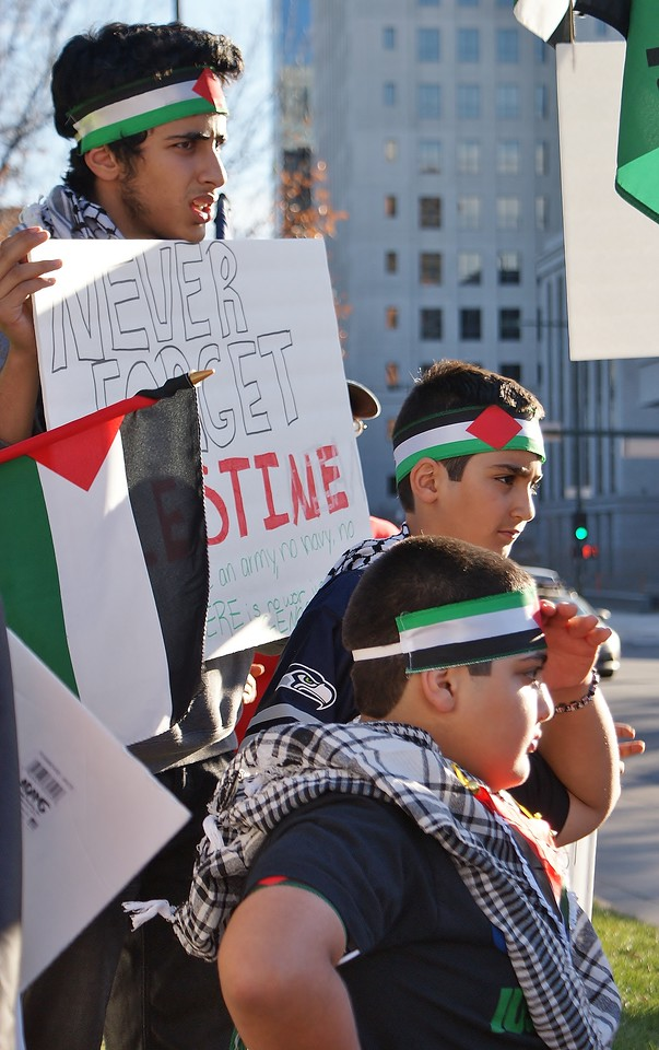 Woman wearing hijab and Palestinian flag scarf gestures while speaking at rally, young boys standing around her.