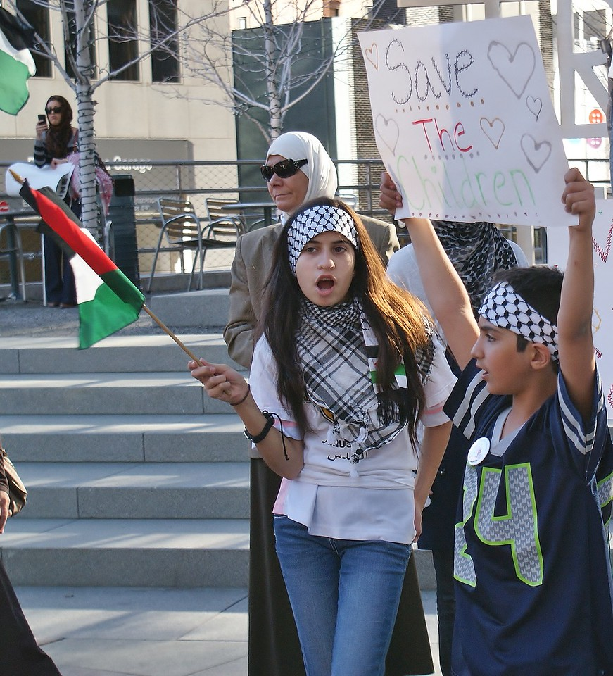 Young girl wearing keffiyeh on head, waving small Palestinian flag, young boy next to her raises sign about children above his head.