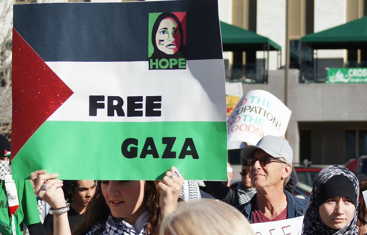 Woman raises Palestinian flag sign above head, other protesters behind her.