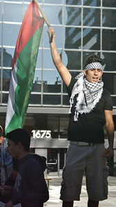 Young man wearing keffiyeh, raises Palestinian flag above head, office building in background.