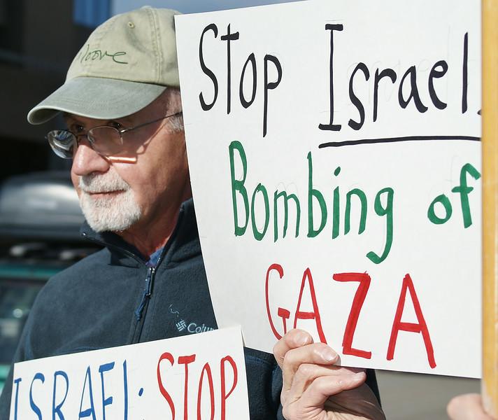 Senior man holding sign  protesting Israeli bombing of Gaza.