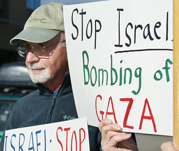 Senior man holding sign  protesting Israeli bombing of Gaza.