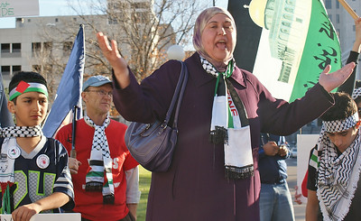 Woman wearing hijab and Palestinian flag scarf gestures while speaking at rally, young boys standing around her, large Palestinian flag with picture of mosque on it, behind her.