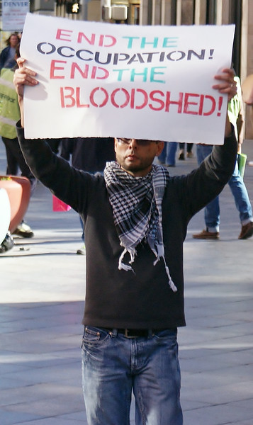 Young man raises sign above head about Israeli occupation of Palestine.