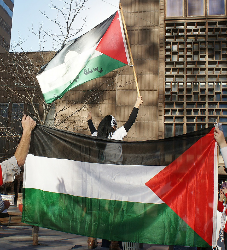 Woman raising Palestinian flag above her head, back to camera, in foreground two people hold large flag.