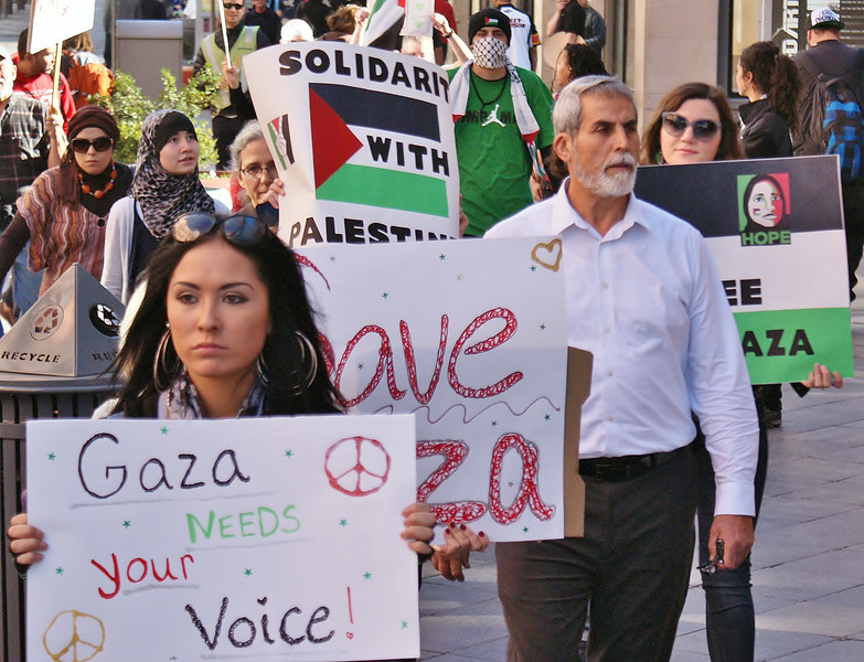 Young woman and senior man marching with signs about Gaza, other protesters in background.
