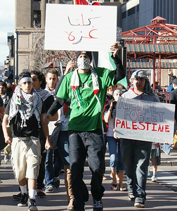 Young man wearing keffiyeh over face, raises sign with Arabic writing on it above head, other protest marchers beside and behind him.