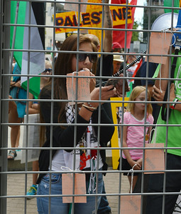 Young woman woman speaking into bullhorn microphone and looking at cellphone,protesters with signs in background, all seen through a wire cage.