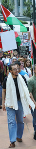 Man with large white scarf around neck, in background, protesters marching with signs and Palestinian flags.