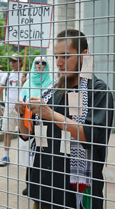 Young man wearing keffiyeh, attaches tag to cage.