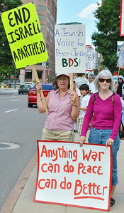 """Two women holding signs about """"apartheid"""" in Israel, one sign says """"Jewish Voice For Peace""""at protest"""