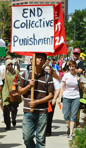 """Young man carries sign, """"End Collective Punishment"""", other protesters  marching in background."""