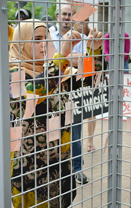 Young woman wearing hijab, hangs tag on wire cage, other tags hanging on it.