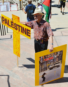 """Senior man holding cross with word """"Palestine"""" written on it, in other hand he holds sign with photograph on it of protester throwing rock at tank"""