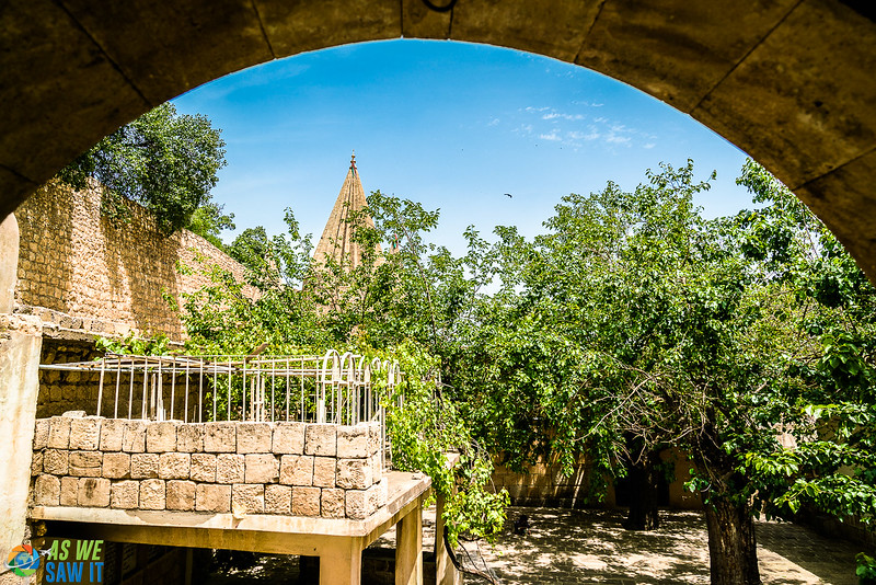 Arch in foreground, with characteristic Yazidi rooftop in the background behind some trees.