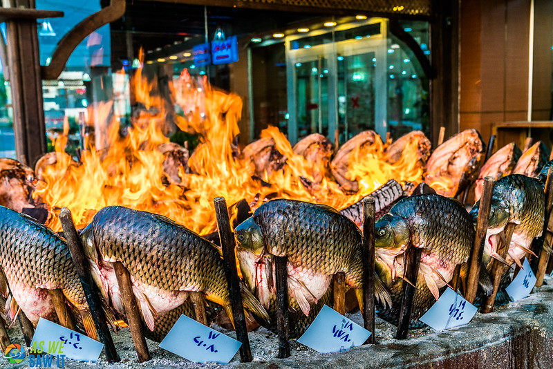 Local fish roasting on skewers around an open fire