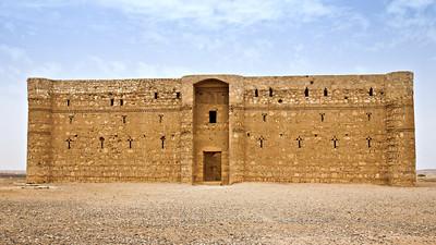 The Qasr Kharana desert castle in Jordan, surrounded by blue skies.