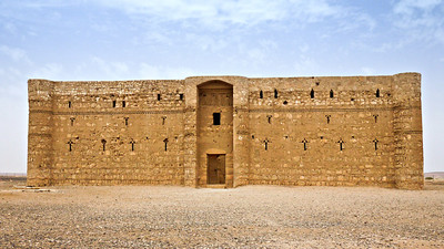 The Qasr Kharana desert castle in Jordan, surrounded by blue skies.