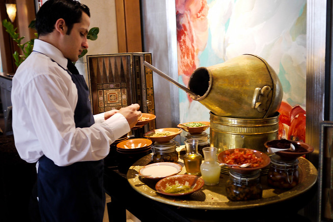 Server at the Four Seasons Amman prepares a bowl of delicious and seasoned foul.