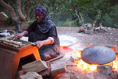 A woman next to a saj, making traditional shrak bread in Ma'in Jordan