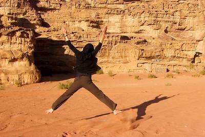Jumping in the red-orange sands of Wadi Rum desert in Jordan.