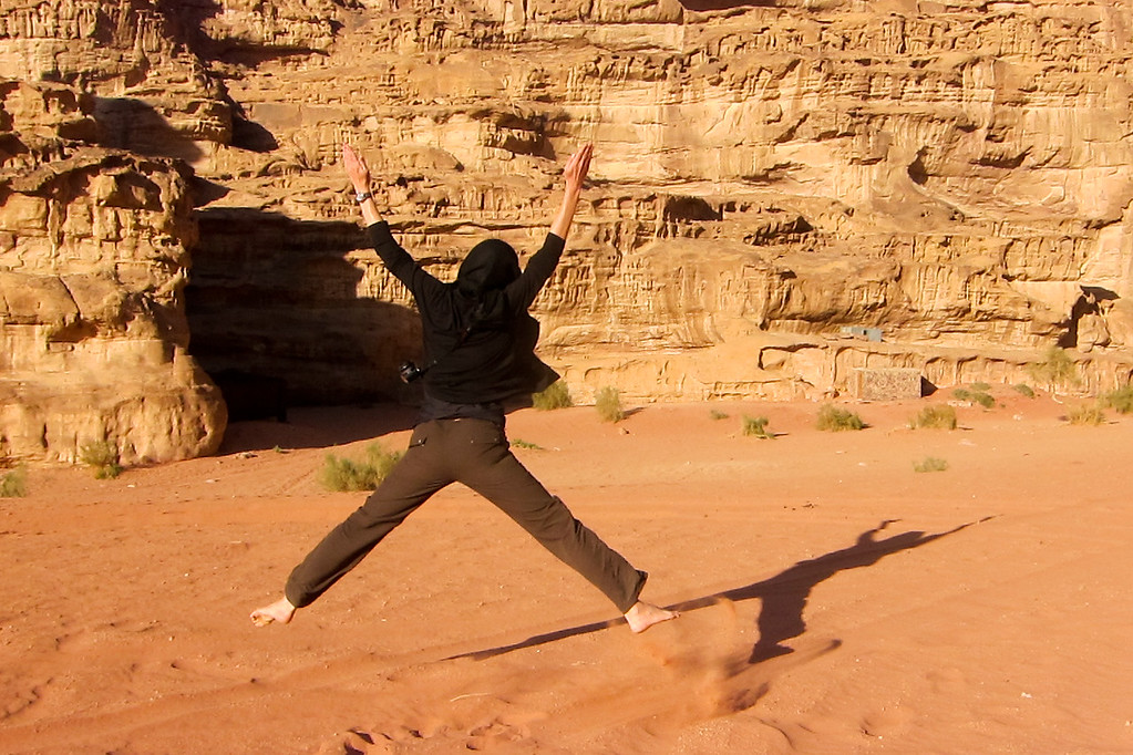 Jumping in the red-orange sands of Wadi Rum desert in Jordan.
