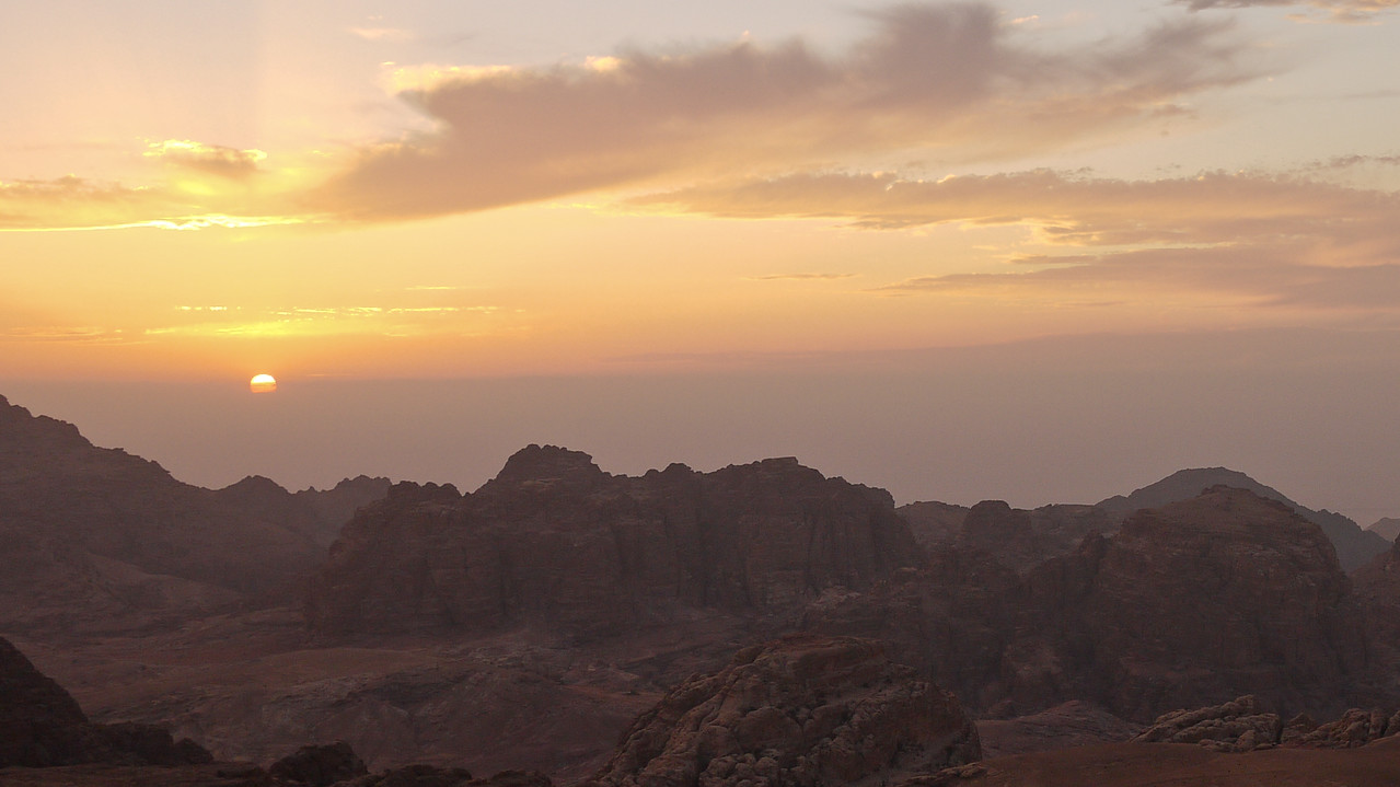 A pinks sunset riots over Petra from a small park in Wadi Musa, Jordan.