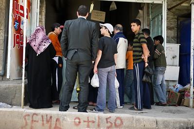 Hordes wait outside a bread shop for fresh pita bread in Jordan