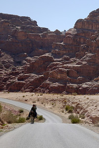 Two boys share a donkey ride out of Petra, Jordan