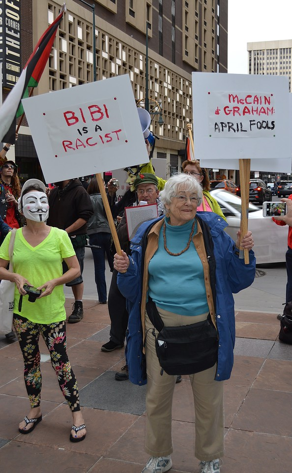 "Senior owmen holds signs ""Bibi Is a Racist"" and ""McCain & Graham, April Fools"", next to her a woman in an anonymous/Guy Fawkes"" mask, in the background other protesters."