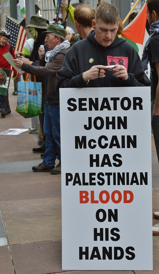 "Man looking at cell phone while holding sign ""Senator John McCain Has Palestinian Blood On His Hands, in the background , other protesters including man speaking into microphone and man wearing ""Guy Fawkes/anonymous"" mask."