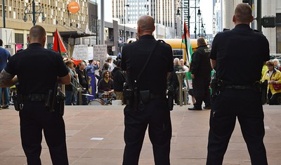 Three police officers standing next to each other, in background, protesters with signs and Palestinians flags.