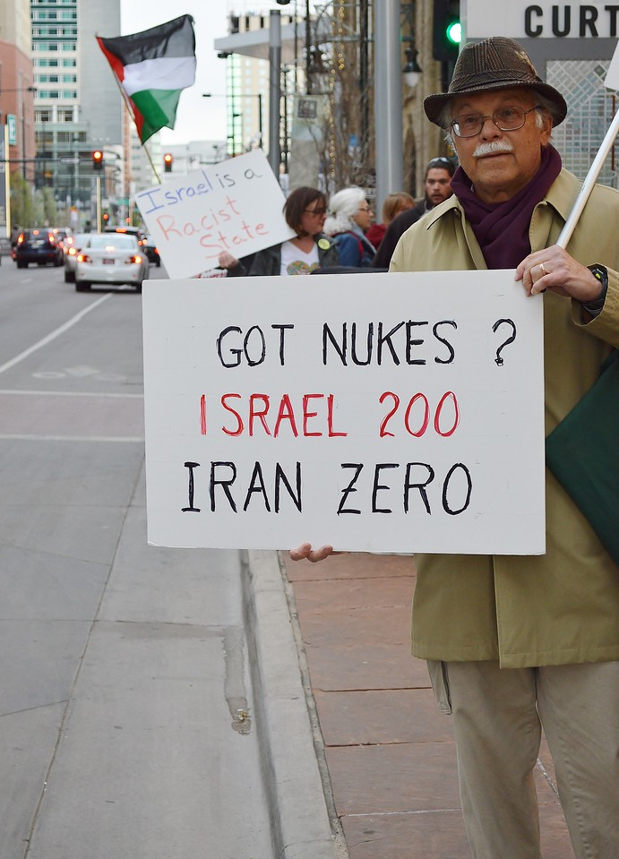 Man next to street holding sign about Israeli nuclear weapons.