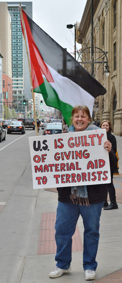 Woman holding sign about US aid and terrorism, Palestinian flag in background.