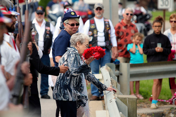 JOHN KLINE | THE GOSHEN NEWS<br /> Middlebury Poppy Queen Berneita Smucker, center, takes part in the annual Memorial Wreath ceremony at the East Warren Street bridge during the Memorial Day parade and ceremony in Middlebury Monday morning.