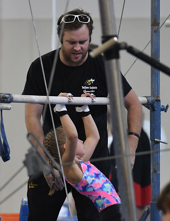 Coach Brian Kormann works with a young student on the bars.<br /> <br /> Photo by JoeBrownPhotos.com