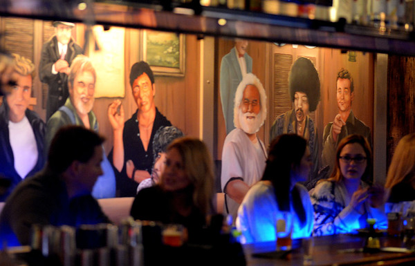 JIM VAIKNORAS/Staff photo A mural of famous and cool people watch behind the bar as patron at Maggie's Farm in Middleton enjoy drinks and food on a crowded Wednesday night.