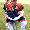 JIM VAIKNORAS/Staff photo Angel's teammates Sarah Aldrich, 8, Celinna Perham, 8, and Gianna Sentner, 7, hug at opening day for the Middleton Little league at the Howe Manning School.
